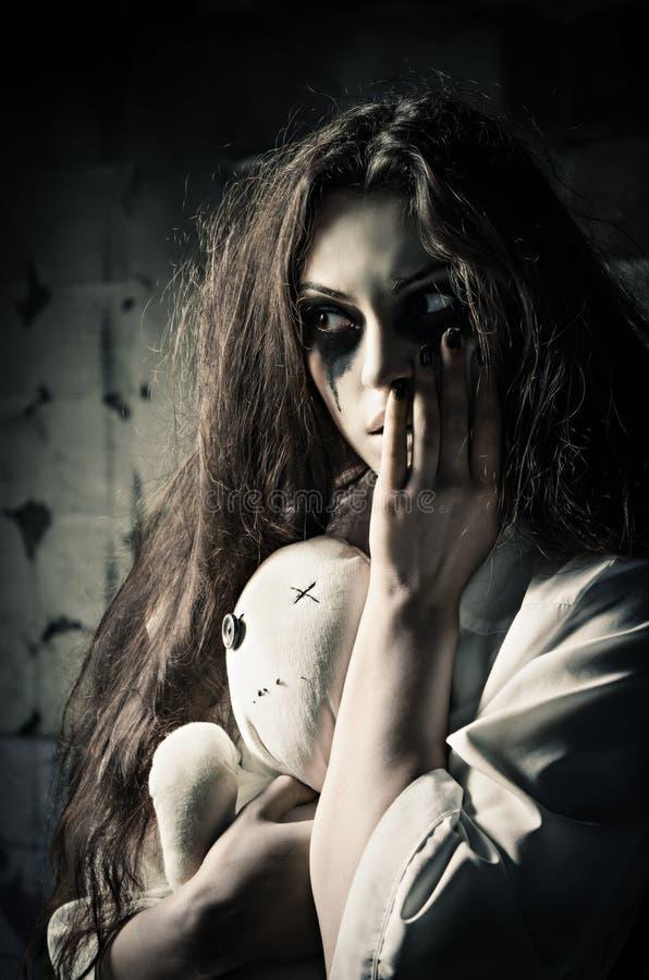 Horroru styl strzelający: dziwaczna smutna dziewczyna z pacynki lalą w rękach obrazy royalty free