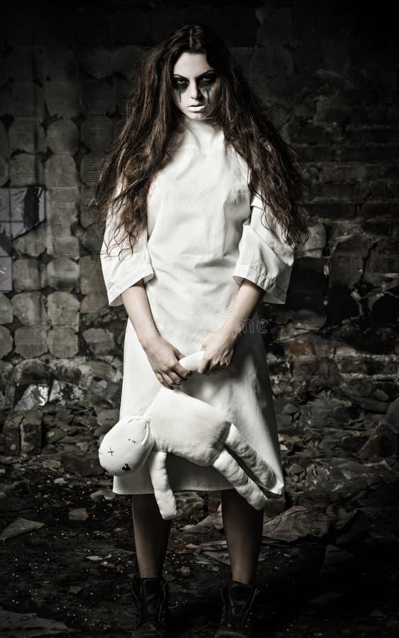 Horroru styl strzelający: straszna potwór dziewczyna z pacynki lalą w rękach obrazy royalty free