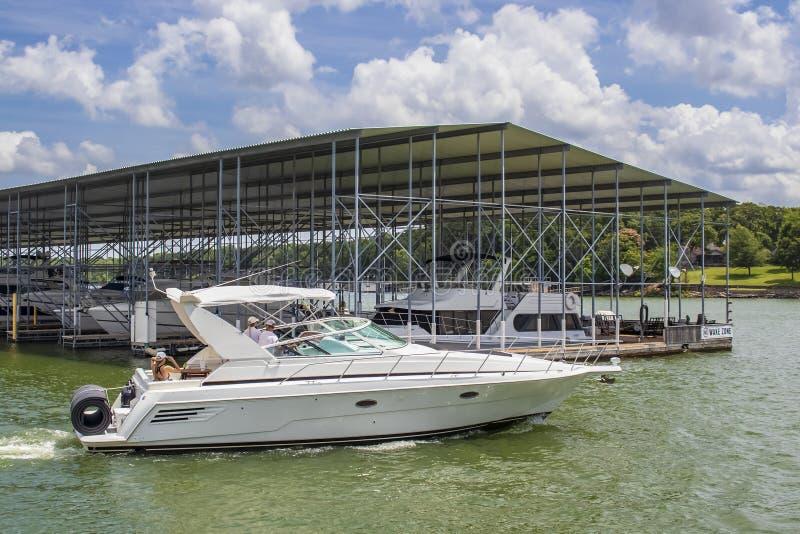 Hors-bord de luxe avec le floatie roulé sur le dos sur le lac en été passant par le dock couvert de bateau avec des bateaux plus  image stock