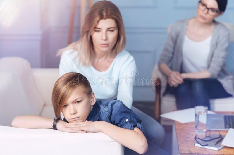 Hors du garçon d'humeur ignorant la maman pendant le seance psychologique photos libres de droits