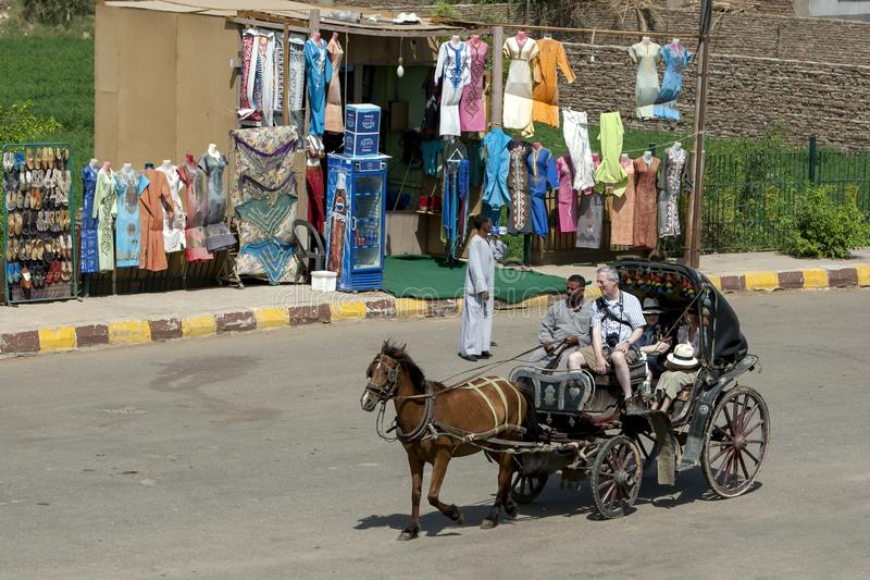 A horse and buggiy ferry a group of foreign tourists in Edfu in Egypt. royalty free stock image