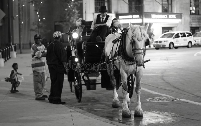 A Horse and Carriage in Downtown Cleveland. Men talk to the driver of a horse and buggy as a little girl waits royalty free stock photos