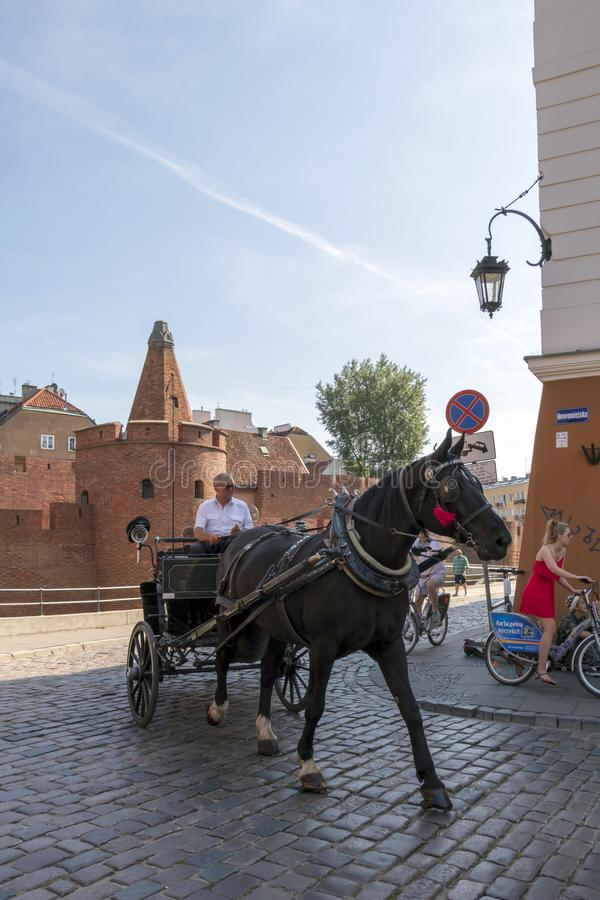 Horse carriage with tourists in the street with Warsaw Barbican in summer sunny day royalty free stock photography