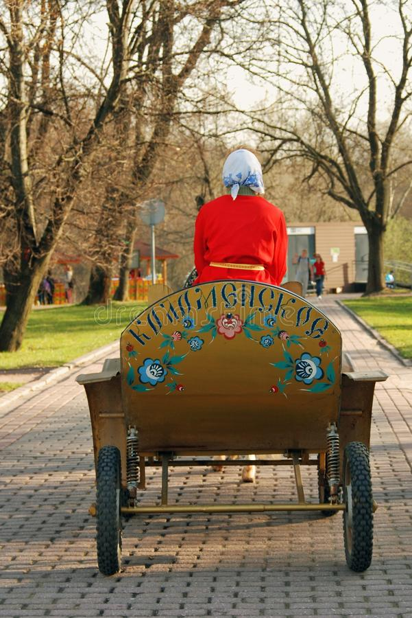 Horse cart carrier - a woman in red. Vintage style horse cart. Early spring nature. Photo taken in Kolomenskoye park in Moscow, Russia. Popular touristic
