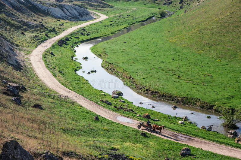 Horse cart moving on an old road near a creek. And a hill royalty free stock image