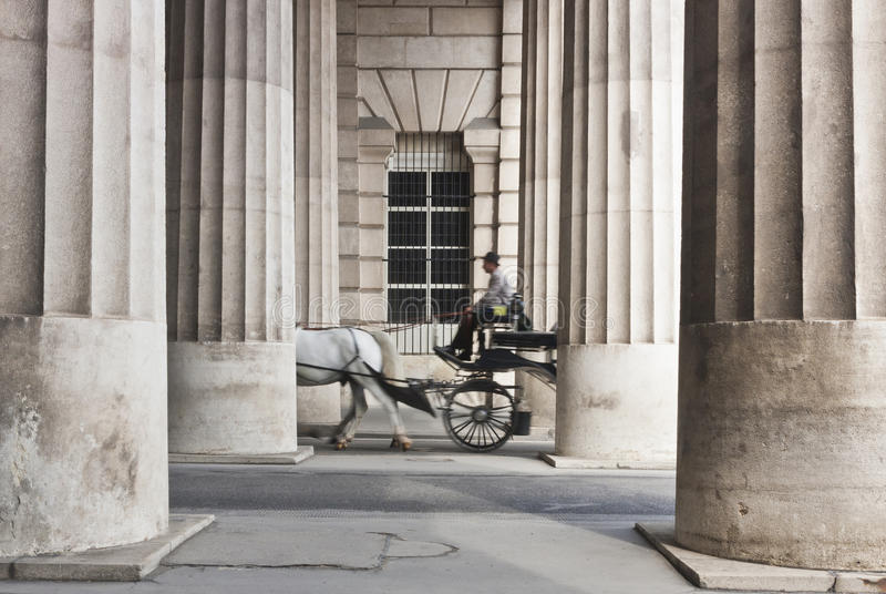 Horse-drawn carriage passing through the collonnade royalty free stock images