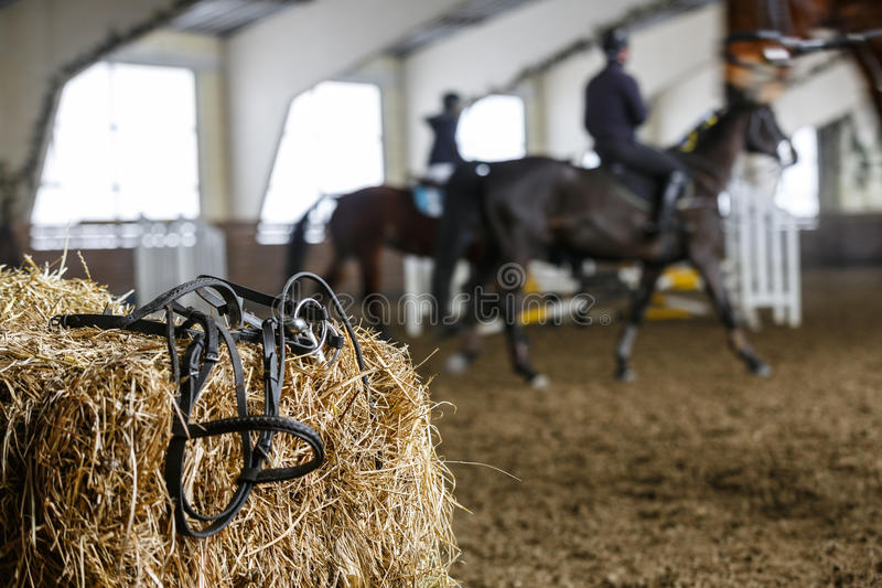Horse equipment and dressage. Horse equipment lying on a fresh bricks of hay on a manege. Blured unrecognizable horse riders on a background stock images