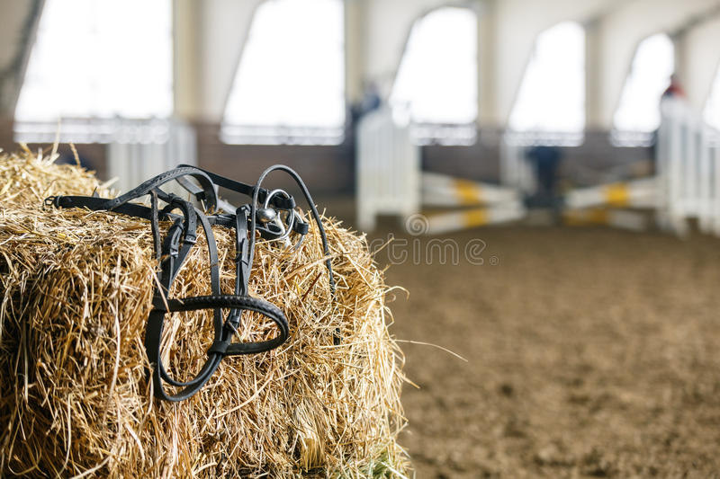Horse equipment on a fresh bricks of hay. Horse equipment lying on a fresh bricks of hay on a manege royalty free stock photo