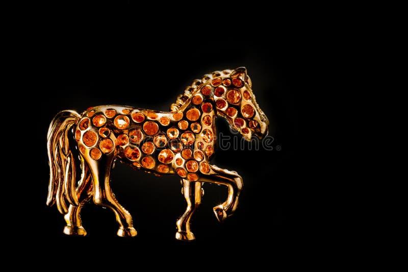 Horse figurine souvenir-nyckelkedja i guldfärgad form med ljusa kulor som skjutits mot en mörk bakgrund stock illustrationer