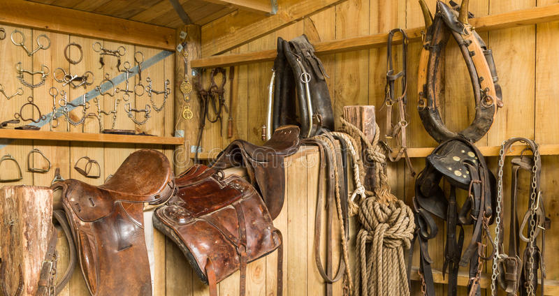 Horse Gear. Horse saddles and other horse gear hanging on a shed wall stock image