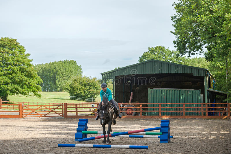 Horse jumping. Young girl practicing horse jumping in outdoor paddock stock image