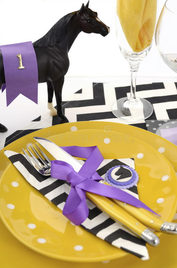 Horse racing carnival event luncheon table place setting. In purple, yellow theme, and black and white chevron strip table runner, vertical royalty free stock images