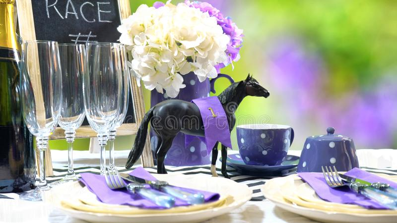 Horse racing Racing Day Luncheon table setting. Horse racing Racing Day Luncheon fine dining table setting with small black fascinator hat, decorations and stock photography