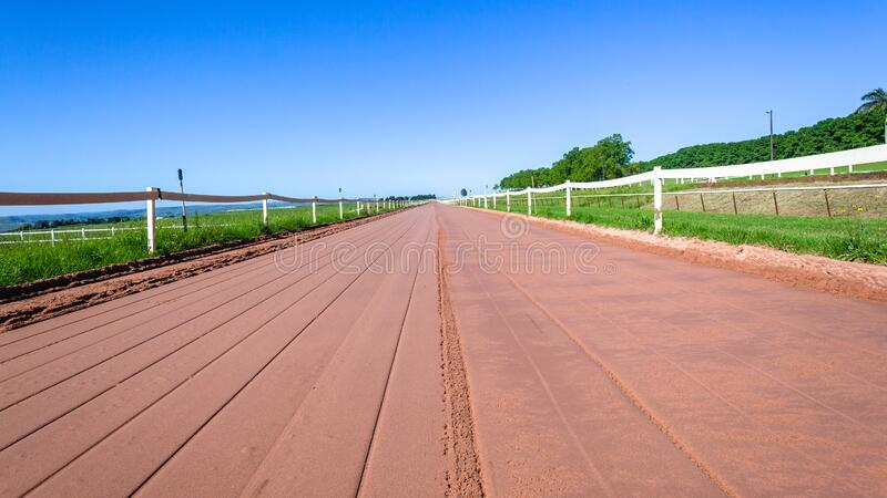 Horse Racing Sand Track Blue Sky Panoramic. Horse racing smooth sand training track for mammals straight looking distant diminishing perspective low photo royalty free stock photography
