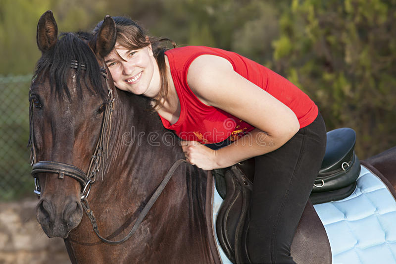 Horse and rider. Woman riding a horse, leaning her head and smiling royalty free stock photos