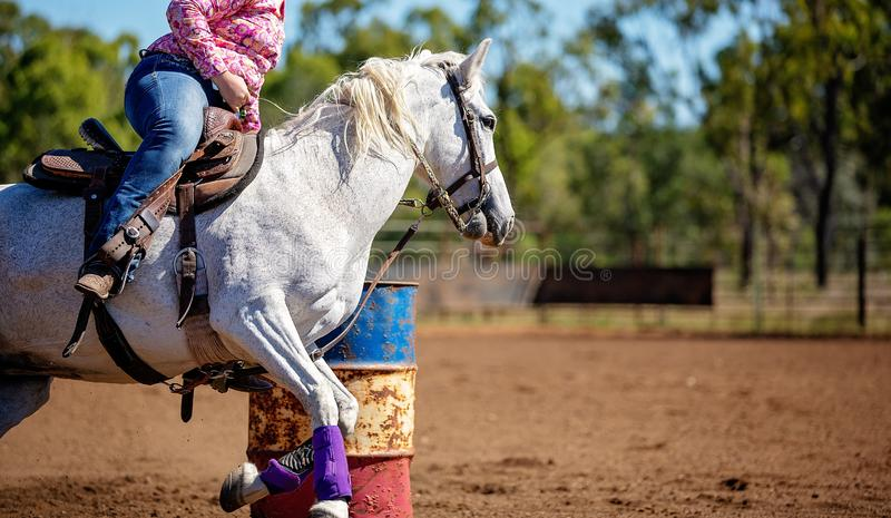 Horse And Rider Competing In Barrel Race At Outback Country Rodeo. Close up of competitor on horseback making a figure eight turn in a barrel race at outback stock photo