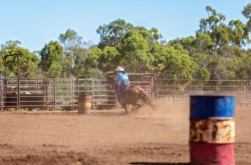 Horse And Rider Competing In Barrel Race At Outback Country Rodeo. Competitor on horseback making a figure eight turn in a barrel race at an outback country stock photography