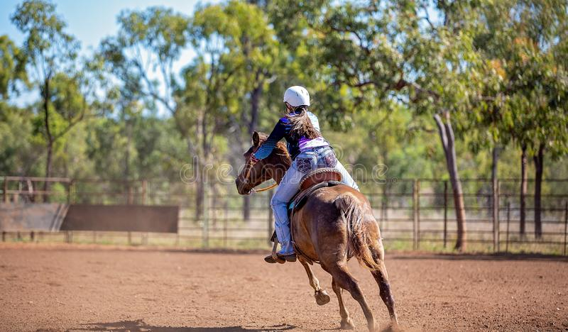 Horse And Rider Competing In Barrel Race At Outback Country Rodeo. Female equestrian competing in barrel racing in dusty arena at outback country rodeo stock photos