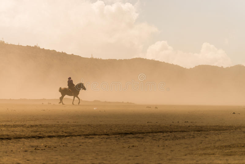 Horse rider desert sand storm. Horse rider riding on desert in sand storm royalty free stock photography