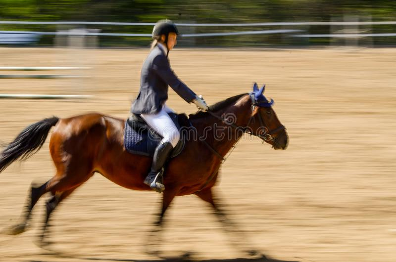 A horse and rider making their way across the show jumping course. Motion blur of a horse and rider making their way across the show jumping course stock image