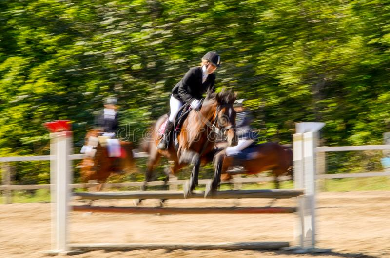 Horse and rider negotiating a show jumping obstacle. Motion blur of a horse and rider negotiating a show jumping obstacle stock images