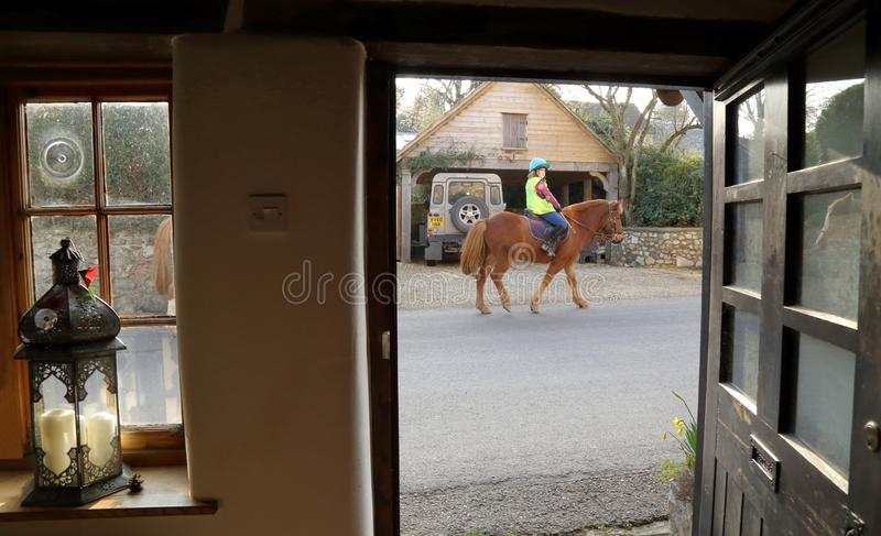 Horse rider on the road. Seen from countryside house in rural Devon