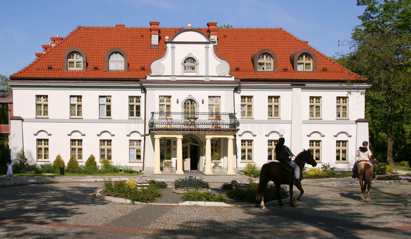 Horse riders and palace. Czarny Las palace in Poland. Beautiful architecture. Equestrians royalty free stock image