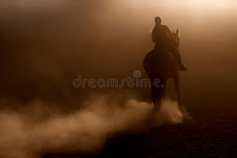 Horse riding in the dust. With backlighting