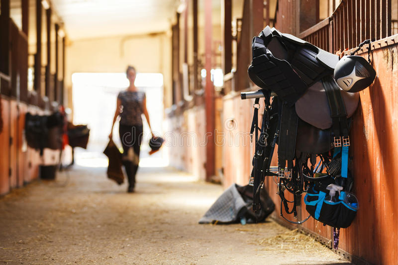 Horse riding equipment. Against the background of the silhouette of a rider in a stable stock photography