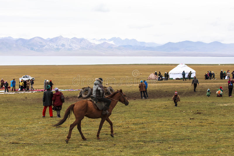 Horse Riding in Song kul Lake in Kyrgyzstan stock photo