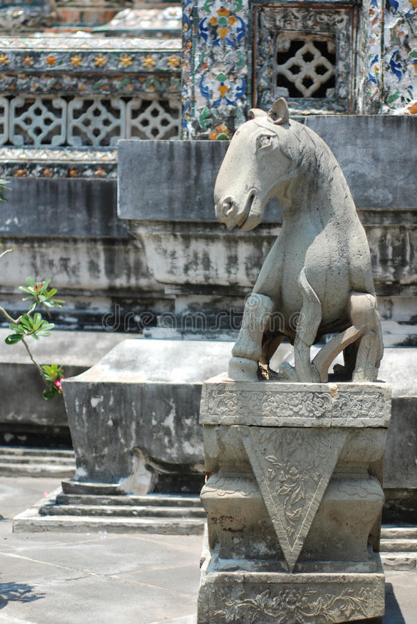 Horse statue at Wat Arun. Wat Arun is among the best known of Thailand's landmarks and the first light of the morning reflects off the surface of the temple with royalty free stock photography