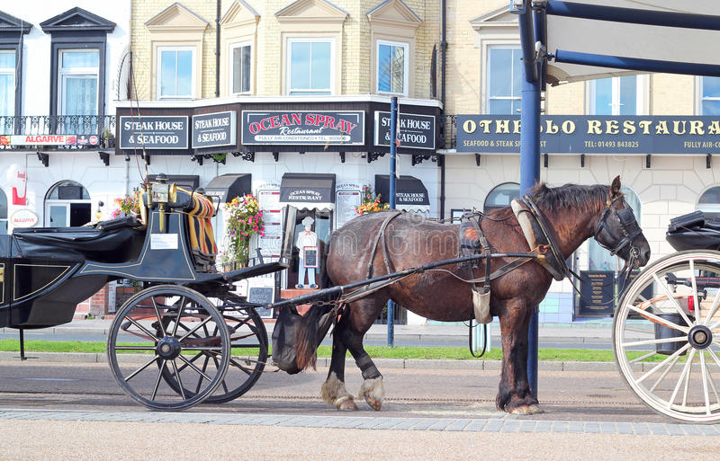 Horse taxi carriages in Great Yarmouth. Horses and carts waiting for fares to taxi people along the sea front in Great Yarmouth United Kingdom stock photography