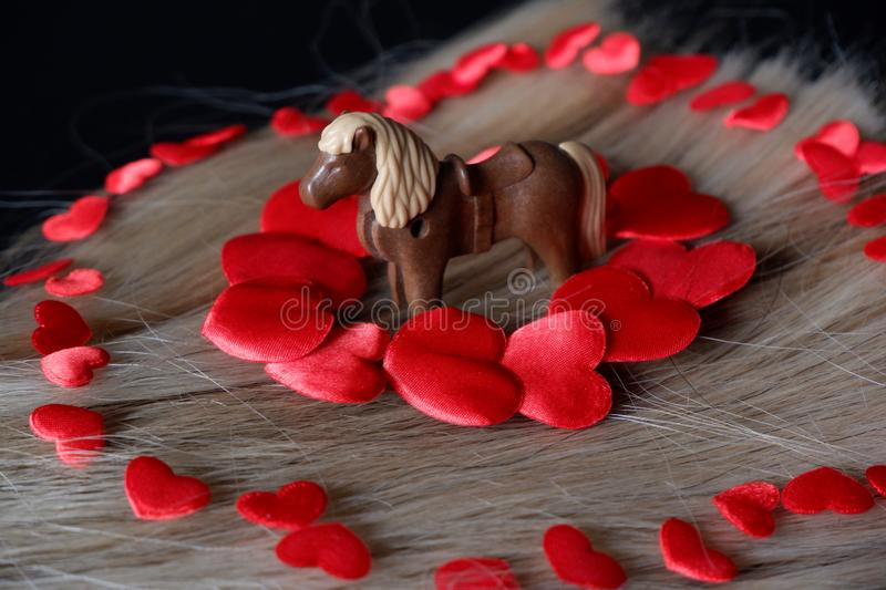Horse surrounded by red hearts on blond horse hair. Horse toy surrounded by red hearts on blond horsehair black background royalty free stock photos
