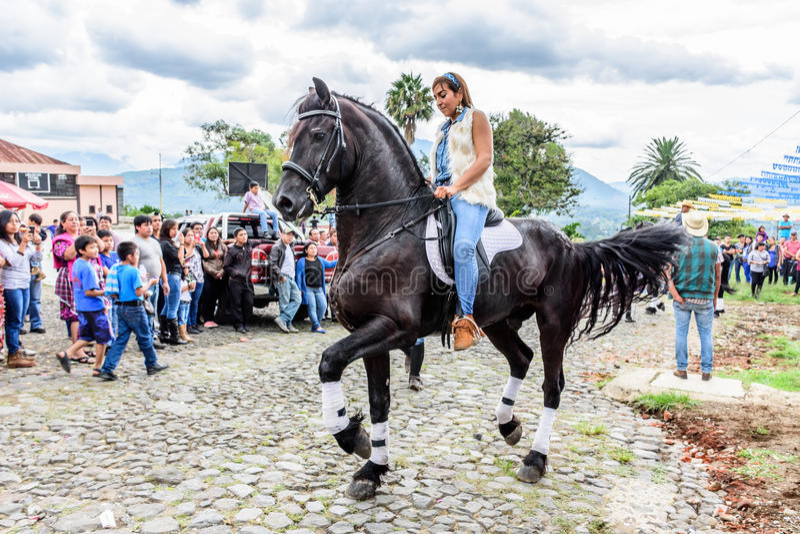 Horseback cowgirl rides in village, Guatemala royalty free stock photography