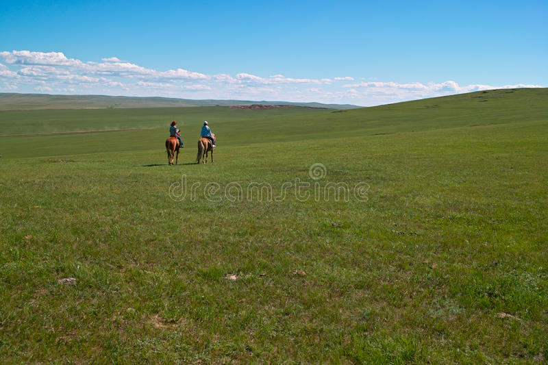 Horseback riders in grassland royalty free stock images