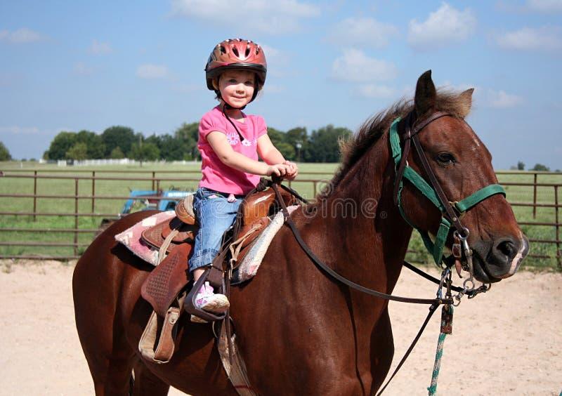 Horseback Riding. A little girls poses on her horse before her horseback riding lesson stock images