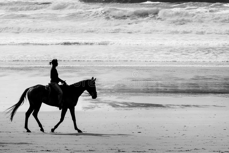 Horseback riding on Cannon beach royalty free stock photography