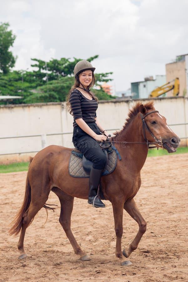 Horseback riding. Girl riding a horse and looking at camera royalty free stock photography