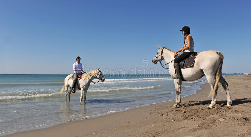 Horseback riding in holidays. A father and his daughter with their horses in holidays stock photography