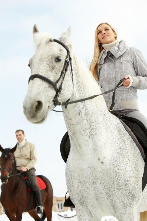 Horsemen. A men and a women riding horses outside, low angle stock photos