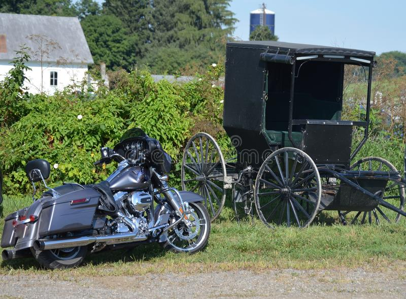 75 horsepower versus 1 horsepower. Old Amish Buggy requires 1 horse while the motorcycle engine has 75 horsepower stock photo