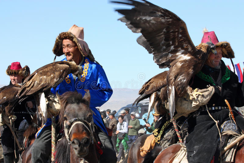 Horseriders in mongolian. MONGOLIA - 25 July 2011, The senior mongolians horsemans in traditional cloathing with golden eagles during the festival July 25, 2011 royalty free stock image