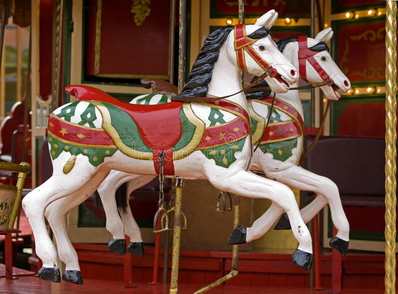 Horses on merry go round. Antique colorful wooden horses of a merry go round on a fair stock photos
