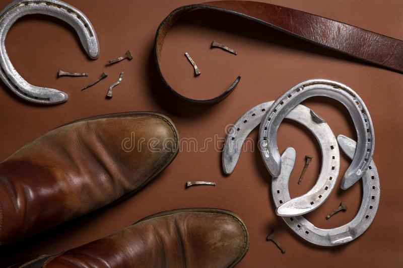 Horseshoes, nails, belt and a pair of leather shoes. On a brown background royalty free stock photography