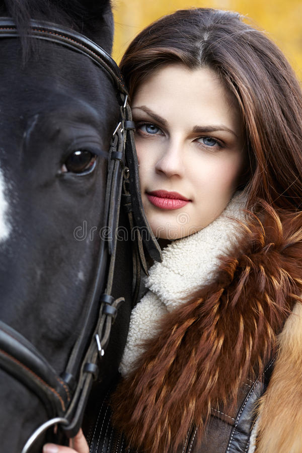 Horsewoman. Portrait of a pretty young woman with a black horse riding autumn day royalty free stock images