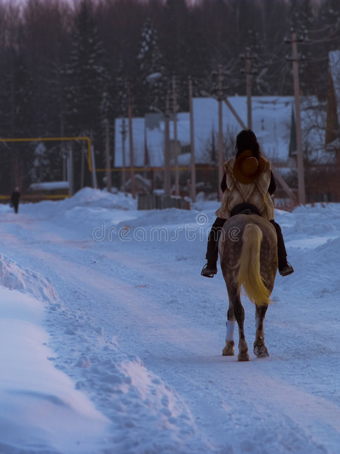 The horsewoman. The brunette rides on a horse into the village stock images