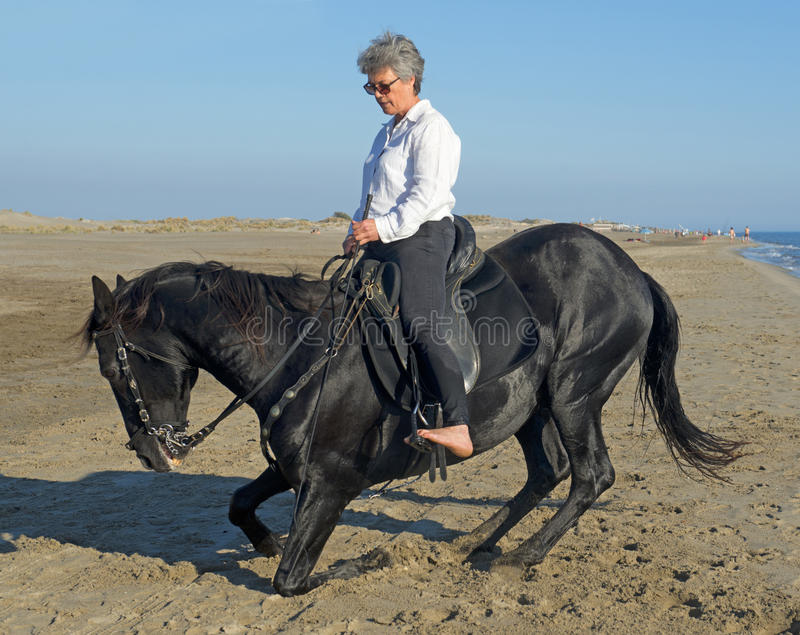 Horsewoman on the beach stock photo