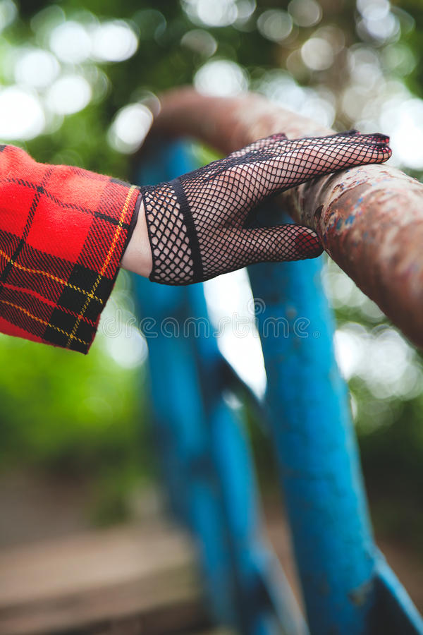 Horsewoman hand in fishnet glove lies on old railing royalty free stock image