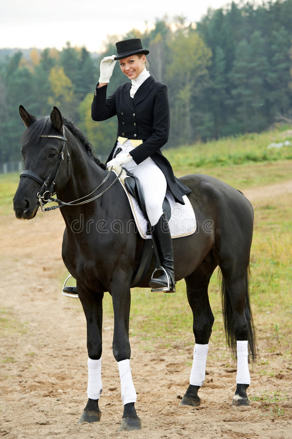 Horsewoman jockey in uniform with horse. Horsewoman jockey in uniform riding horse outdoors stock photography