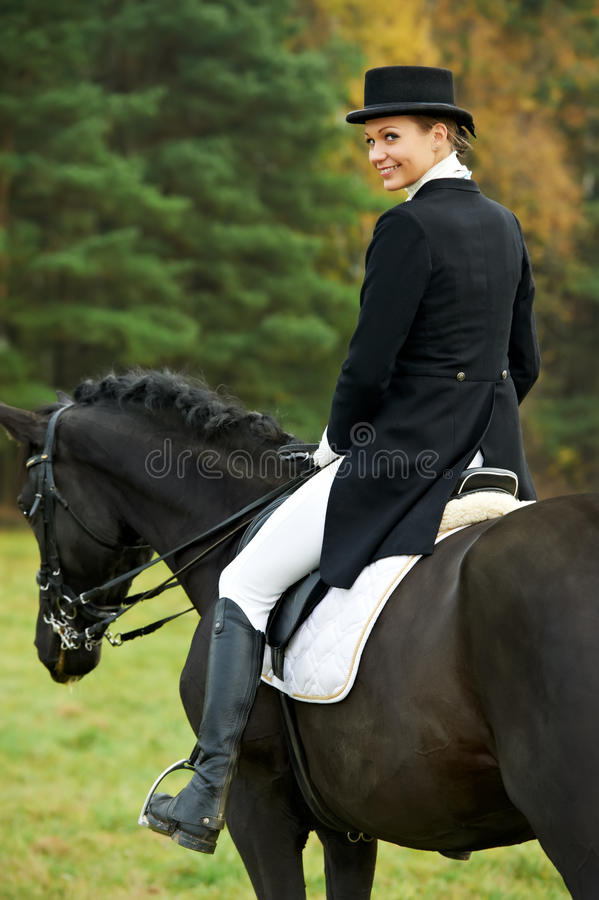Horsewoman jockey in uniform with horse stock images
